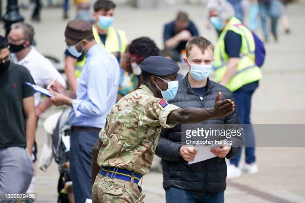 Soldiers from the Royal Horse Artillery guide members of the public at a rapid vaccination centre, set up outside Bolton Town Hall on June 09, 2021...