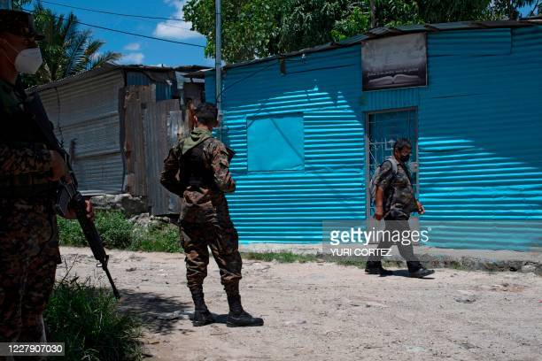 Soldiers from the Salvadoran air force paratrooper battalion stand guard at the December 1 community in Soyapango, El Salvador, on July 30 amid the...