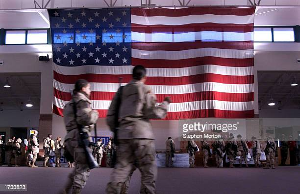 S soldiers from the Third Infantry Division walk past a huge US flag in the deployment center at Hunter Army Airfield January 19 2003 in Savannah...
