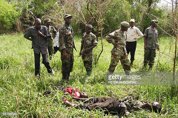 Soldiers from the Uganda People's Defense Forces look at the bodies of two rebels belonging to the Congolese Allied Democratic Force that were killed...