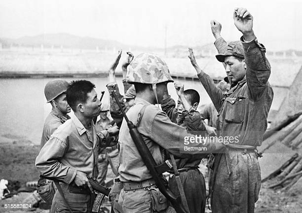 Soldiers from the United Nations Armed Forces search captured North Korean soldiers during the Korean War landing at Inchon, 1950.