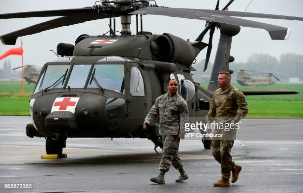 Soldiers from the US Army 1st Cavalry Brigade 1st Cavalry Division walk past a UH60 Black Hawk helicopter on the tarmac at Shape Airfield at Chievres...