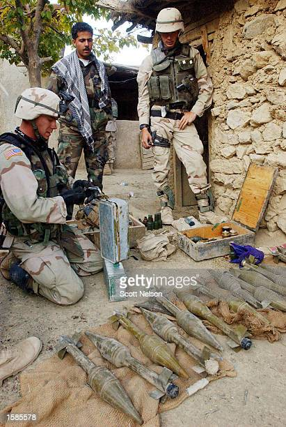 Soldiers from the U.S. Army 82nd Airborne Division sort through a weapons cache discovered during a November 2, 2002 sweep of homes in the village of...