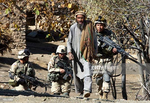 Soldiers from the U.S. Army 82nd Airborne escort a local Afghan man to a holding area while they conduct a sweep of homes November 2, 2002 in the...