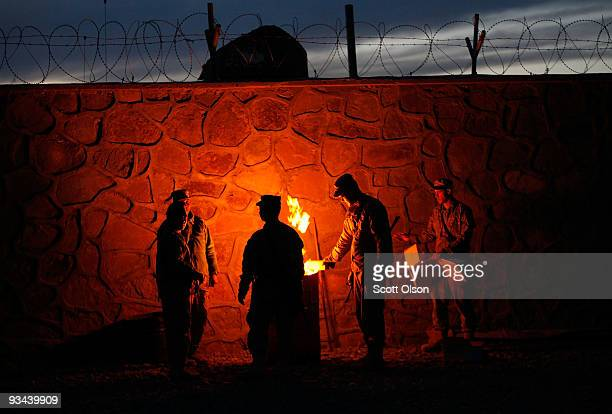 Soldiers from the US Army's 1st Battalion 501st Parachute Infantry Regiment and Afghan National Police huddle around a burning barrel late in the...