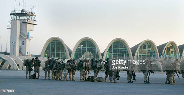 Soldiers from the US Marine Corps line up on the tarmac to board a C130 cargo plane as they depart Kandahar air base February 4 2002 in Afghanistan...
