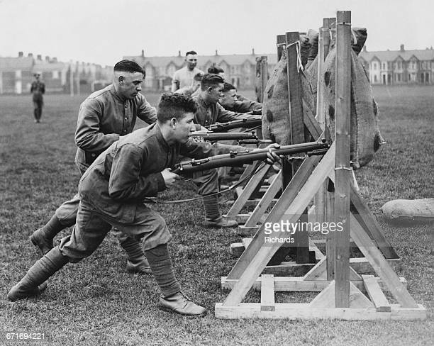 Soldiers from the Welch Regiment undertake bayonet thrust practice against straw filled dummies using the Short Magazine Lee–Enfield Mk III 303 bolt...