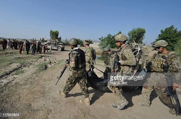 US soldiers from Viper Company 126 Infantry carry a body bag containing confiscated weapons and ammunition during a housetohouse search at a village...