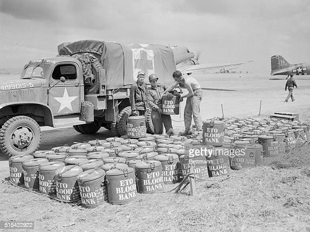 Soldiers gather drums of donated blood near a personnel carrier on a makeshift tarmac during World War II.