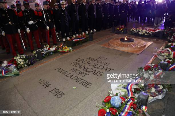 Soldiers gather during a wreath laying ceremony beside the eternal flame of The Unknown Soldier at The Arc de Triomphe in Paris on November 9 to...