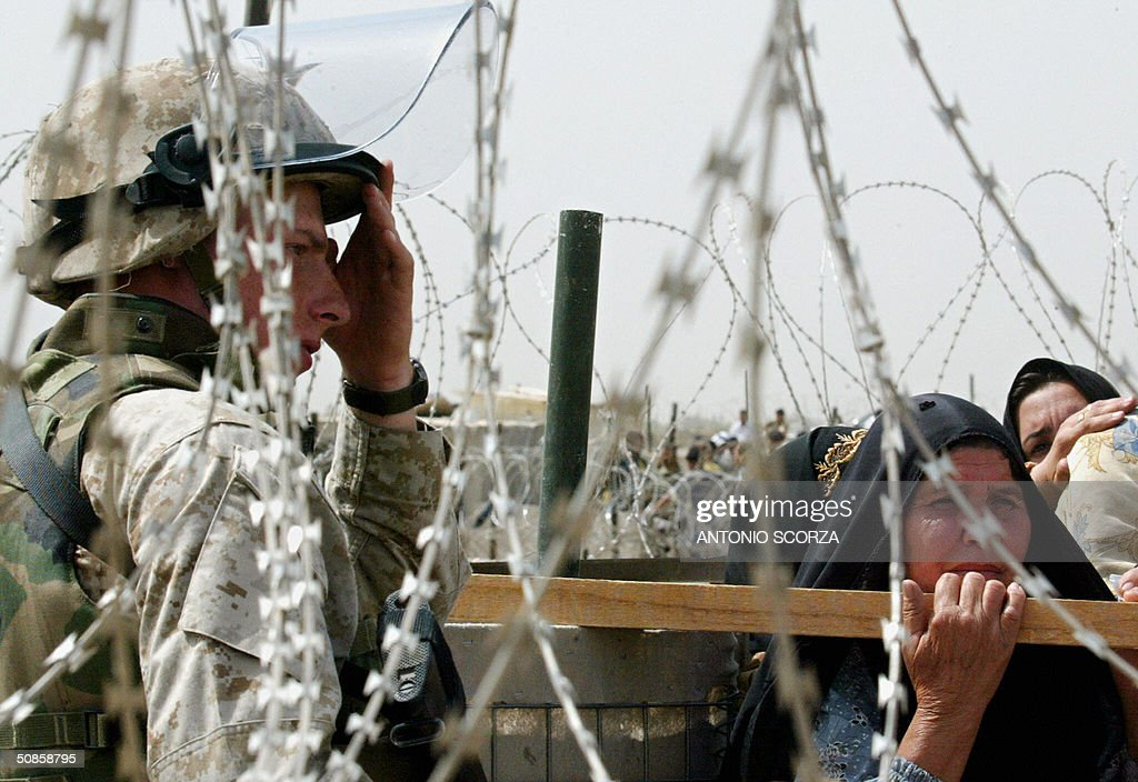A US soldiers gestures as he controls the entrance of the Abu Ghraib prison, 20 May 2004 where Iraqi people are gathering in hope of getting information about their loved ones held by US forces at the detention center, 30 kms west of Baghdad. US troops faced further embarrassment amid claims they killed dozens of people at a wedding celebration in a remote western Iraqi town, at a time when the occupation forces are already reeling from a prison abuse scandal. AFP PHOTO/Antonio SCORZA
