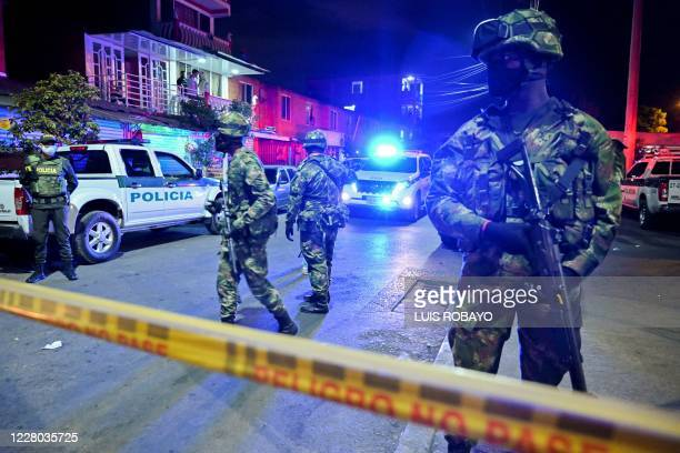 Soldiers guard the area where an explosive device exploded in Aguablanca district in the east of Cali Colombia on August 13 near the site of the...