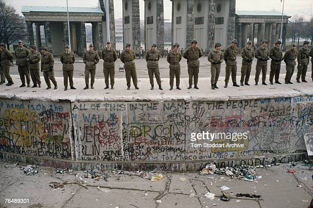 Soldiers guard the Berlin Wall on tha day following its fall with the Brandenburg Gate in the background 10th November 1989