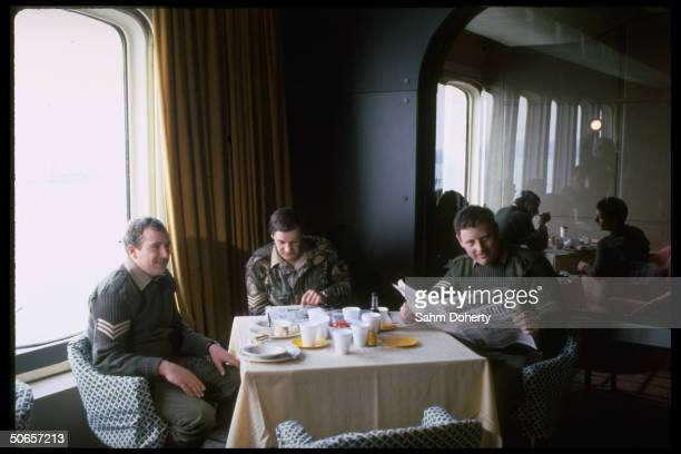 Soldiers having lunch & reading paper aboard QE2 before sailing to Falklands