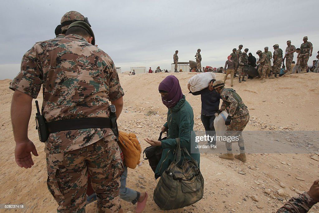 Soldiers help Syrian refugees who have arrived at the Jordanian military crossing point of Hadalat at the border with Syria after a long walk through the Syrian desert on May 4, 2016 in Hadalat, Jordan. Coming from the cities of Raqaa, Deir Al-Zor and Hama, roughly 300 hundred refugees crossed into Jordan at Hadalat on Wednesday, while over 5000 refugees crossed in the last four days coming from Aleppo.
