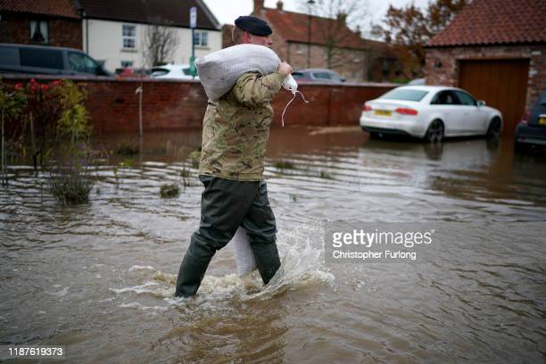 Soldiers help with sandbagging homes in the village of Fishlake which continues to suffer from flooding and residents start to salvage belongings...