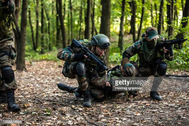 soldiers helping out to wounded friend - army training stock pictures, royalty-free photos & images