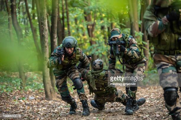 soldiers helping out to wounded friend - special forces stock pictures, royalty-free photos & images