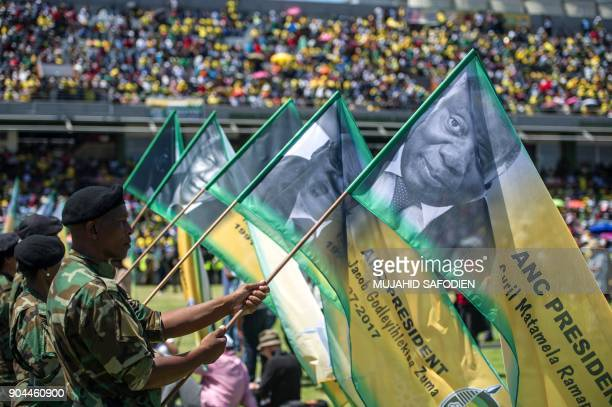 Soldiers hold banners bearing portraits of the former and current ANC presidents during the African National Congress's 106th anniversary...