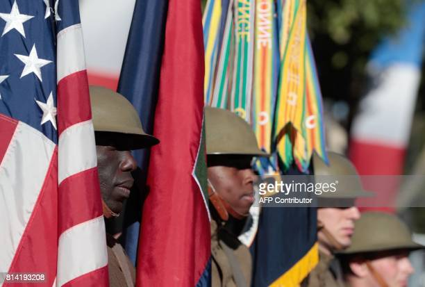 US soldiers hold flags as they prepare for the start of the annual Bastille Day military parade on the ChampsElysees avenue in Paris on July 14 2017...