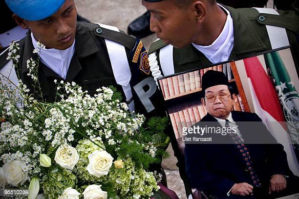 Soldiers hold pictures at the State funeral for former Indonesia president Abdurrahman Wahid in his East Java hometown on December 31 2009 in Jombang...