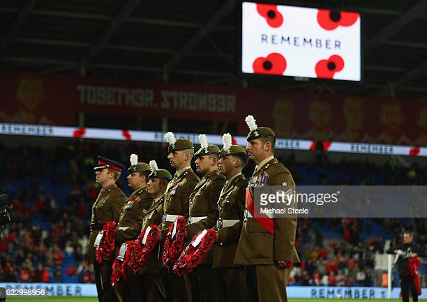 Soldiers hold poppy wreaths ahead of the teams entering the field of play during the FIFA 2018 World Cup Qualifier between Wales and Serbia at...
