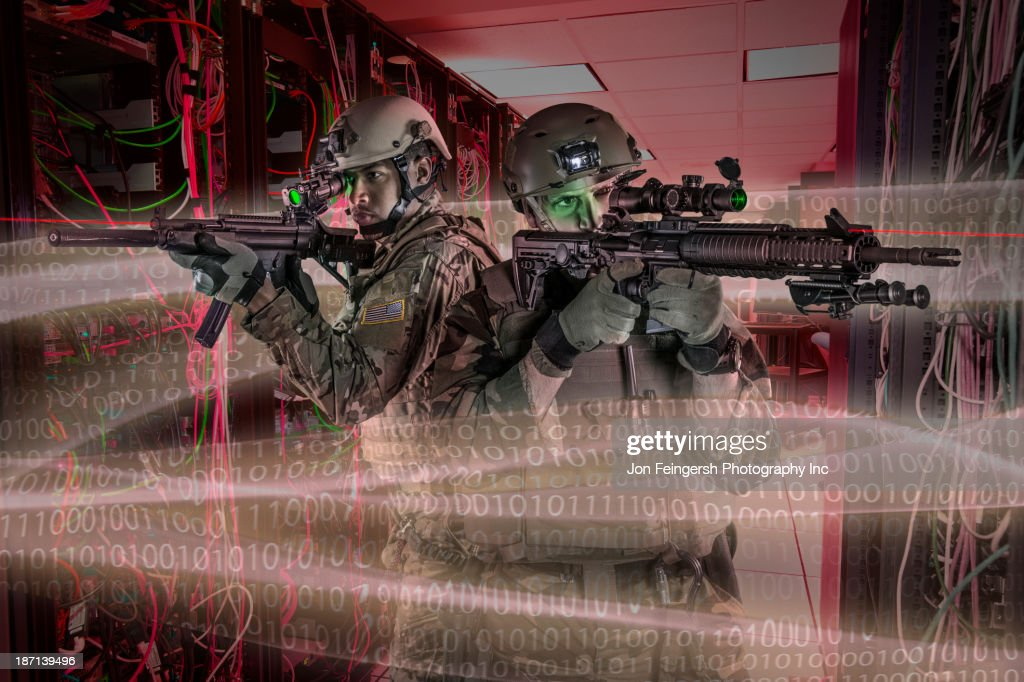 Soldiers holding guns in server room : Stock Photo