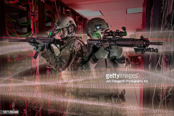 Soldiers holding guns in server room
