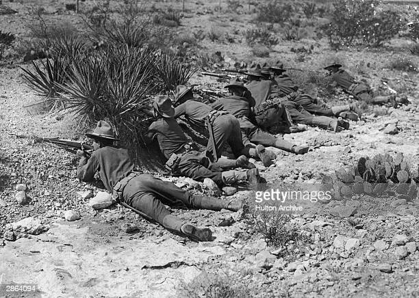 Soldiers in a barren landscape take cover and aim their rifles during the SpanishAmerican War 1898