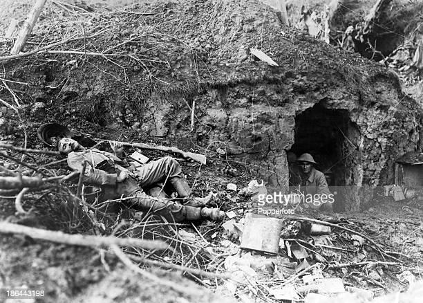 Soldiers in a cave with a casualty of war lying where he fell in Flers France during World War One circa 1918