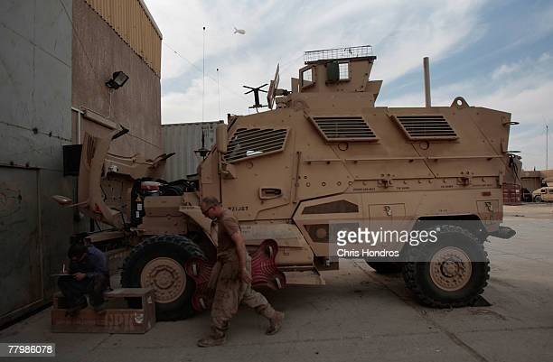 Soldiers in a maintenence company in the US Army's 212 infantry walk past on of their new MRAP vehicle November 19 2007 at Forward Operating Base...
