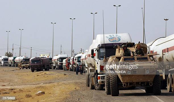 Soldiers in a US Army assault vehicle wait 05 July 2003 as they prepare to escort a convoy of propane gas oil and gasoline tanker trucks south on the...