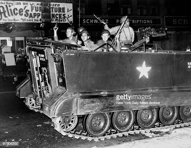 Soldiers in an armored personnel carrier patrol the streets of Newark during race riots