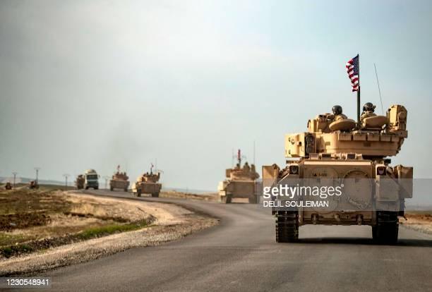 Soldiers in Bradley tanks patrol an area near Syria's northeastern Semalka border crossing with Iraq's Kurdish autonomous territory, on January 12,...