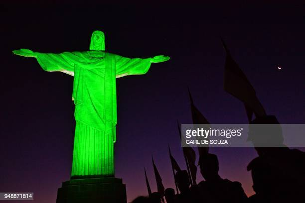 TOPSHOT Soldiers in ceremonial costume line up in front of Christ the Redeemer statue after it was lit green to mark the National Army day in Rio de...