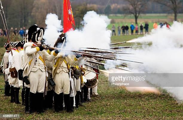 soldados en la histórica regimentals muskets de salida de disparo - imperialismo fotografías e imágenes de stock
