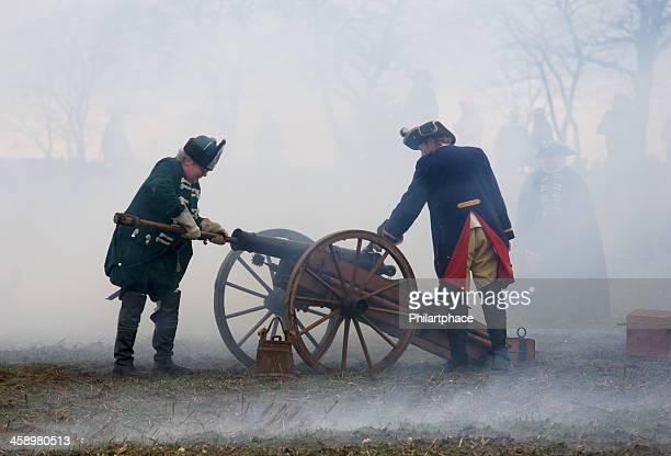 Soldados no histórico regimentals com medieval cannon