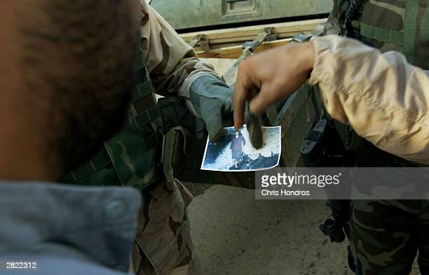Soldiers in the 4th Infantry Division show an Iraqi man a photo of a suspected militant during a morning raid December 19, 2003 in Samarra, Iraq....
