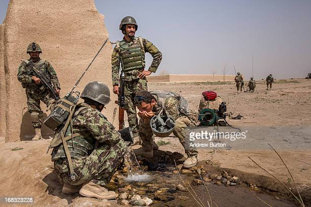 Soldiers in the Afghan National Army's 6th Kandak , 3rd company, drink water from a well during a joint patrol with U.S. Forces near Command Outpost...
