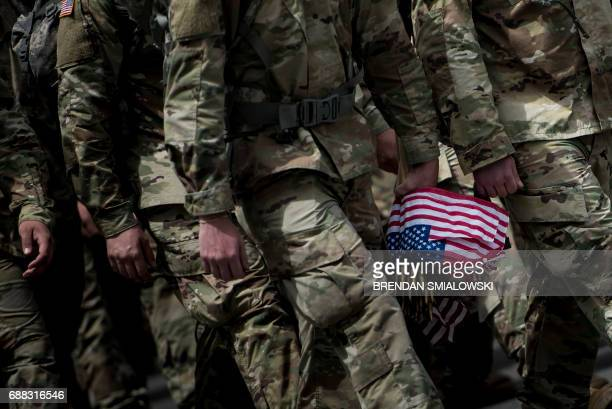 Soldiers in the Old Guard arrive to place flags at graves in Arlington National Cemetery during 'Flags In' in preparation for Memorial Day May 25...