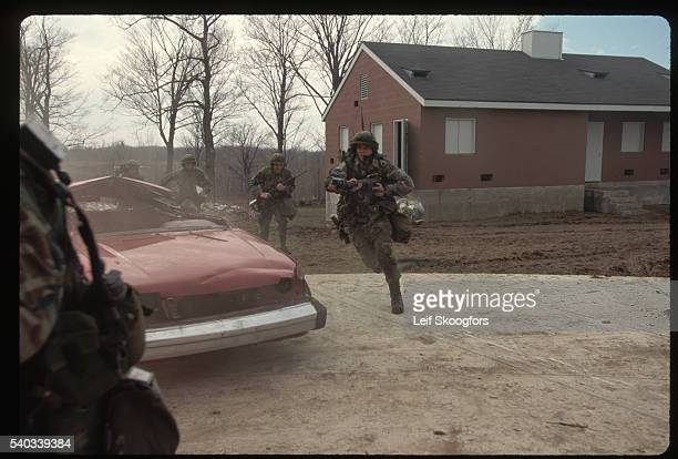 Soldiers in training at Fort Drum New York run past a smoking car during combat exercises intended to teach methods of fighting in settled areas