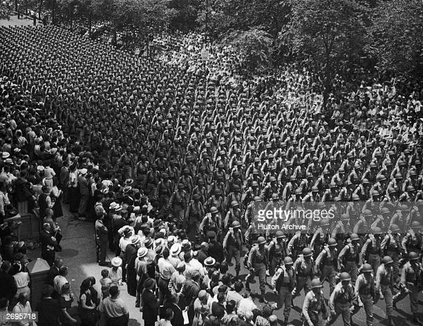 US soldiers in uniform march in rows down Fifth Avenue during a World War II victory parade in Manhattan New York City
