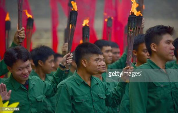 Soldiers in Vietcong uniforms hold torches during a ceremony marking the 50th anniversary of the Tet Offensive in Ho Chi Minh City on January 31 2018...