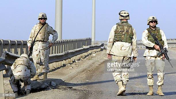 US soldiers inspect a crater in the ground caused by an improvised explosive device attack on a US military convoy early 05 December 2003 in Baghadad...