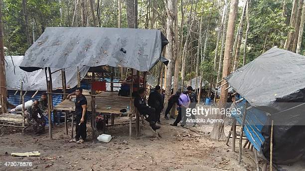 Soldiers inspect abandoned huts after finding a jungle camp believed used by human traffickers to withhold Rohingya migrants at a mountainous forest...