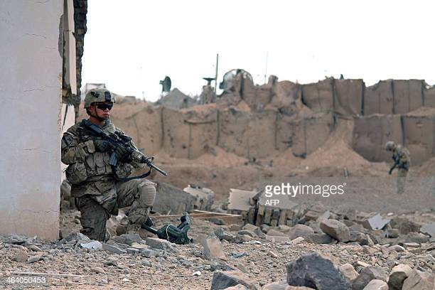 US soldiers inspect the scene of a suicide attack outside a base in Zhari district Kandahar province on January 20 2014 Nine Taliban militants...
