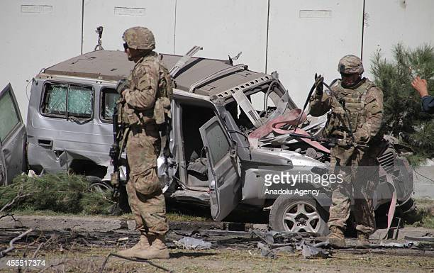 US soldiers inspect the site of a suicide car bomb attack targeting NATO convoy on a busy road that runs from the US Embassy to the airport in Kabul...