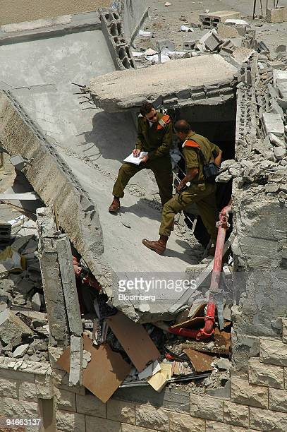 IDF soldiers inspect the site where rockets hit a house yesterday in Safed village in Upper Galilee Israel Friday July 14 2006 Israel pounded...