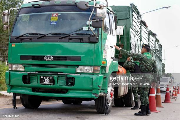 Soldiers inspect trucks at a checkpoint in search of ethnic Uighurs who escaped from an immigration detention centre in Sadao district in the...