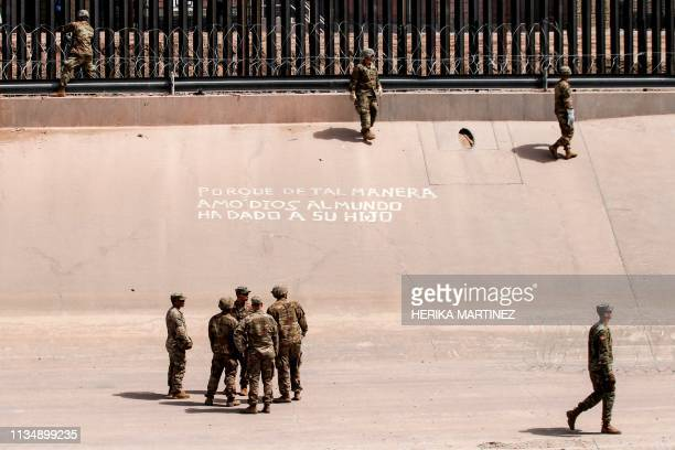 US soldiers install barb wire by the USMexico border fence reading Because in such way God has loved the world he has given his son in El Paso Texas...